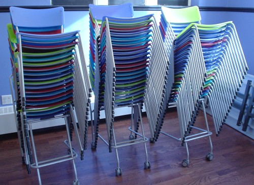 Wheeled carts hold dozens of multicoloured plastic occasional chairs