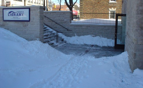 Snow-covered footpath leads to well-cleared walkway between stairs and open door