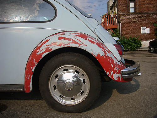 Baby-blue Volkswagen Beetle's rear fender shows scratchy patches of red primer