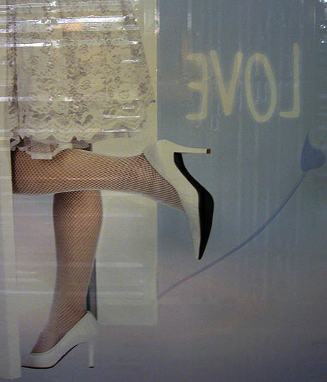 Corner of a wall poster shows the word LOVE backwards and a woman in a lacy white skirt and white fishnets kicking up one heel