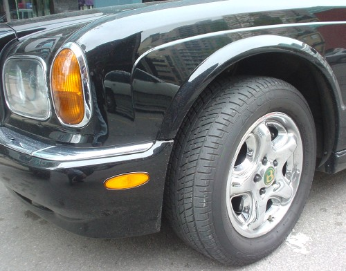 Front-left five-pointed silver wheel and massive tire of parked black Bentley