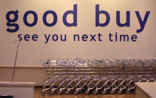 Giant letters on wall read 'good buy' and 'see you next time' and are almost as tall as the shopping carts parked below them