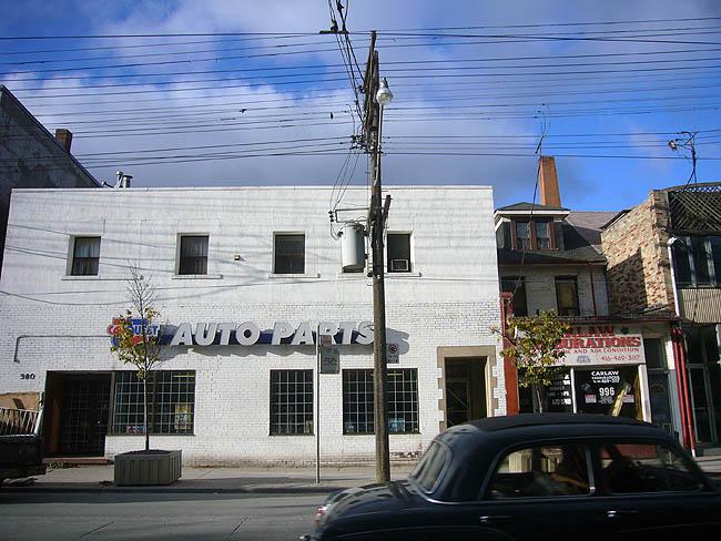 Square old car whizzes past auto-parts store