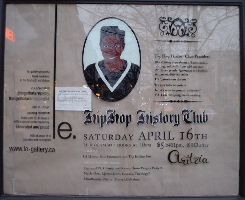 Glossy glass pane (with paper behind it) of Aritzia window shows man in cardigan and, among a lot of other copy, HipHop History Club in blackletter