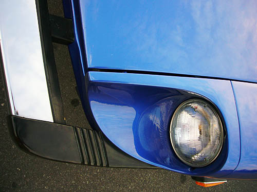 From overhead, a headlight sits inset into the top of a rounded-edged corner on a blue car