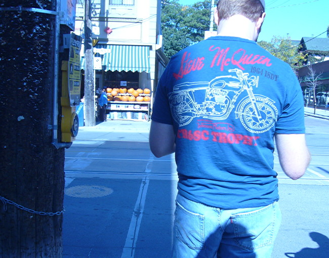 Blue-tinted picture of young man in T-shirt that reads Steve McQueen CR6SC Trophy and shows a motorcycle