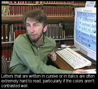 Screenshot of bearded man seated at large-screen monitor with enlarged text. Caption reads: Letters that are written in cursive or in italics are often extremely hard to read, particularly if the colo[u]rs aren't contrasted well