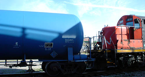 Orange-and-black CN locomotive is coupled to brilliant blue tanker car