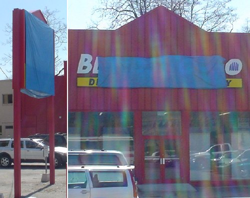 Signs on convenience store hastily covered with blue tarpaulin