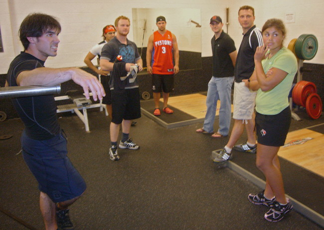 Five athletes in weightroom, along with Florian and James, turn toward right of camera