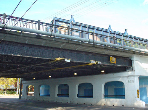 A train's freight car sits atop a plaster-covered white overpass at an angle to a city street