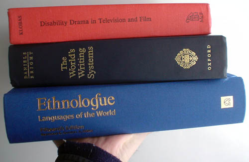 Hand holds up three hardcover books: 'Disability Drama in Television and Film,' 'The World's Writing Systems,' 'Ethnologue: Languages of the World'