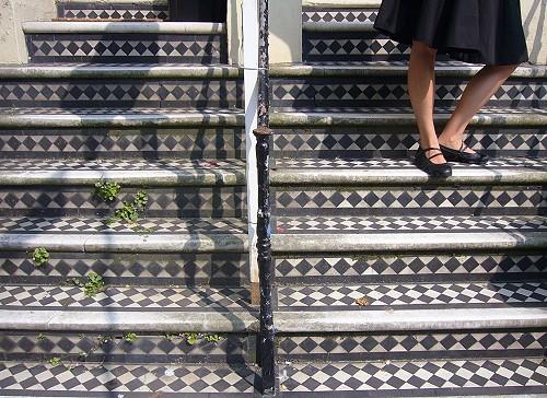 Mysterious woman in black skirt walks down diamond-patterned staircase made of marble and terrazzo