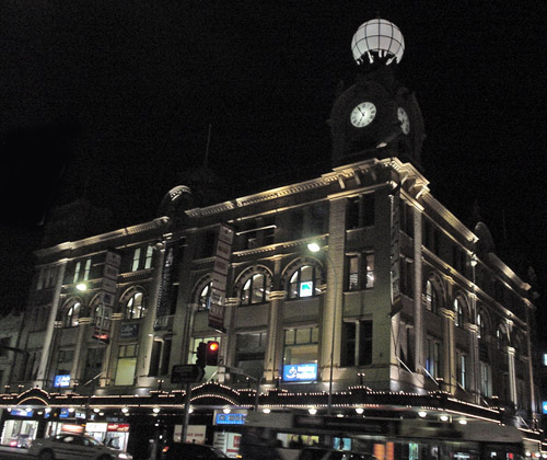 Nighttime view shows four-storey, ornate, well-lighted building with a projecting clock tower