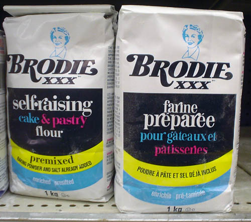 Side-by-side flour bags use gay swash typography to render the labels BRODIE XXX™ self-raising cake & pastry flour and farine préparée pour gâteaux et pâtisseries
