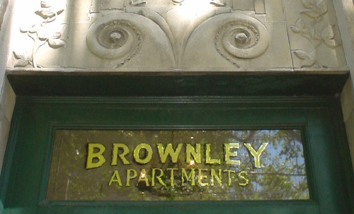 Hand-painted letters on transom window read BROWNLEY APARTMENTS