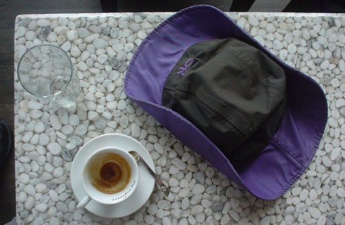 Overhead photo of used espresso cup, empty glass, and purple-and-black Gore-Tex hat on white-pebbled tabletop