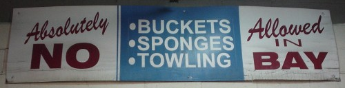Sign reads 'Absolutely no •buckets •sponges •towling allowed in bay'