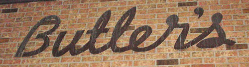 Sign attached directly to brick wall reads 'Butler's' in script
