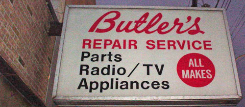 Illuminated sign projecting from wall reads 'Butler's' in script plus 'REPAIR SERVICE Parts Radio/TV Appliances ALL MAKES'