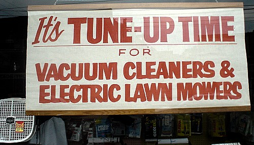 Hand-painted sign: It's TUNE-UP TIME FOR VACUUM CLEANERS & LAWN MOWERS