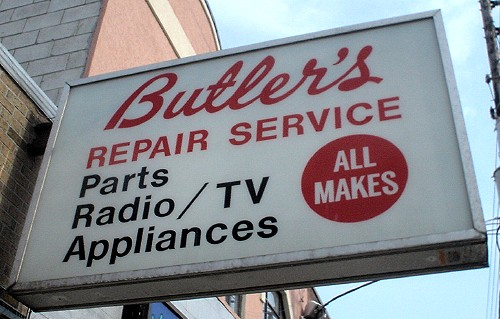 White sign projecting from building reads Butler's in script and REPAIR SERVICE Parts Radio/TV Appliances ALL MAKES in Helvetica