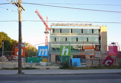 Construction site at dusk shows glass-fronted four-storey building and skewed, falling-down italic letters on rotated signs on the front fence: a m h c