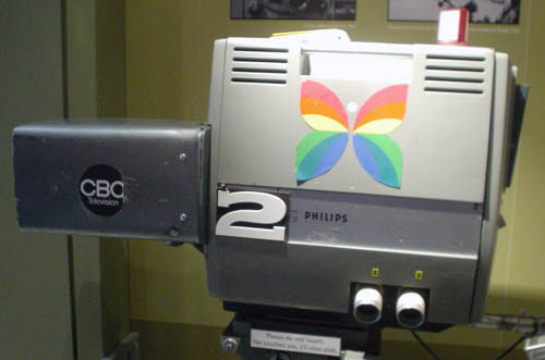 Large studio camera is labelled CBC 2 with a paper cutout butterfly with rainbow-coloured wings