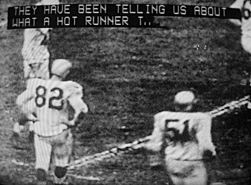 Black-and-white football game with two lines of captioning at top reading THEY HAVE BEEN TELLING US ABOUT WHAT A HOT RUNNER T