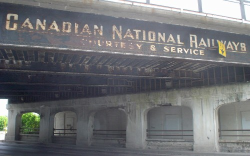 Railway overpass above a road reads CANADIAN NATIONAL RAILWAY COURTESY & SERVICE in distressed white letters