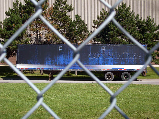 Blue transport trailer seen through a chain-link fence has faded legend CONSUMERS