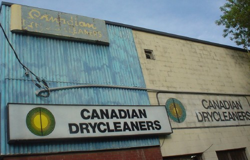 Two signs reading 'Canadian Drycleaners' in Helvetica adorn a building. At top, an old, faded, decrepit sign says the same thing, with 'Canadian' written in script