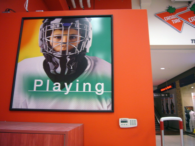 "Giant red sign on Canadian Tire inside wall shows child in hockey mask with the letterspaced Helvetica word ""Playing'"