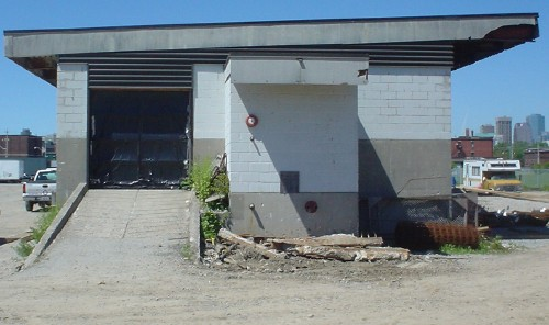 Side view of angle-roofed cinder-block building with ramp, vehicle bay, and affixed red fire bell