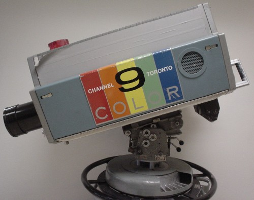 Vintage studio television camera is rectangular with a protruding round lens and CHANNEL 9 TORONTO COLOR written on coloured bands on the side