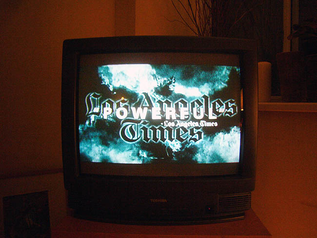 Television set in darkened red room shows Univers type on top of blackletter