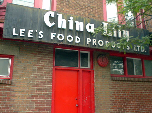 Black sign over red door on brick building reads China Lily LEE'S FOOD PRODUCTS LTD.