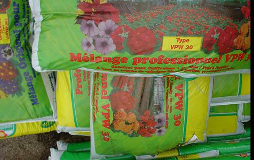 Green fertilizer bags show red flowers and have screaming red type in Cooper Black