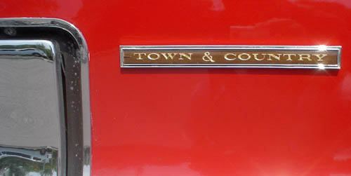 Glittering name badge on red car reads TOWN & COUNTRY in yellow on woodgrain