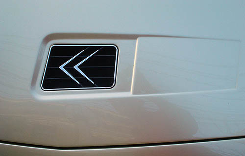 Recessed panel on hood of champagne-coloured car shows a pair of steel chevrons mounted on a black background