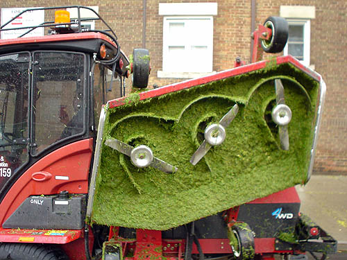 Red, tractor-sized industrial lawnmower has blade pulled up to reveal a uniform coating of green grass on the underside
