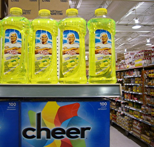 Four brilliant yellow-green bottles of Mr. Clean on a shelf above rich blue Cheer box, with an aisle of canned goods nearby