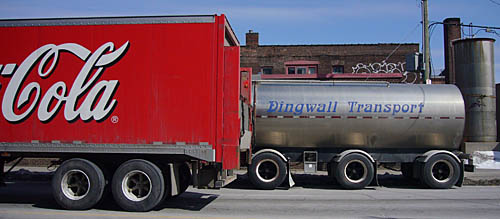 Red Coca-Cola truck passes silver tanker labelled Dingwall Transport in slanted Arnold Böcklin type