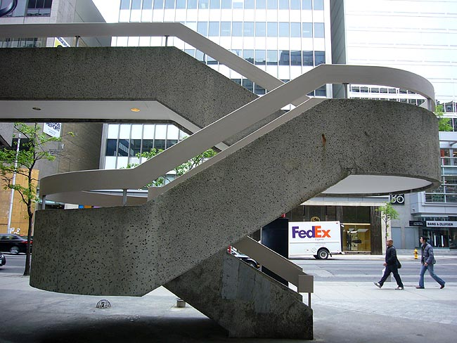 Grey concrete staircase on street twists once, then twice as it rises a single storey