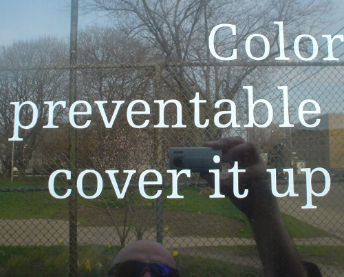 My camera, head, and shades are reflected in a sign fragment that reads 'Color preventable cover it up'
