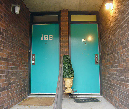 Two green front doors are numbered 122 in an OCR-like font and 121 in metal adhesive numbers