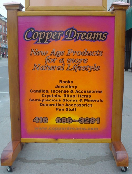 Pink, gold, and yellow sandwich-board sign with script and italic type: 'Copper Dreams: New Age Products for a more Natural Lifestyle'