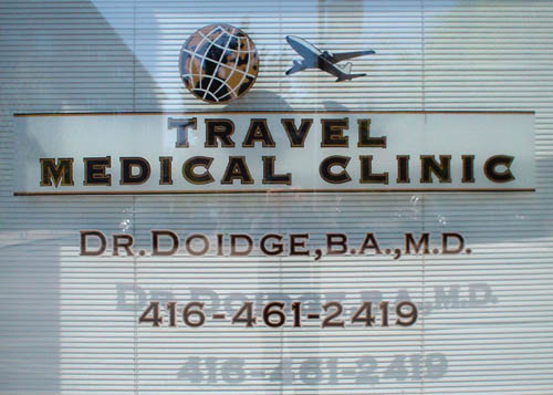 Shop window in front of closed Venetian blinds reads TRAVEL MEDICAL CLINIC Dr. Doidge, b.a., m.d. in bold and book-weight bank gothics