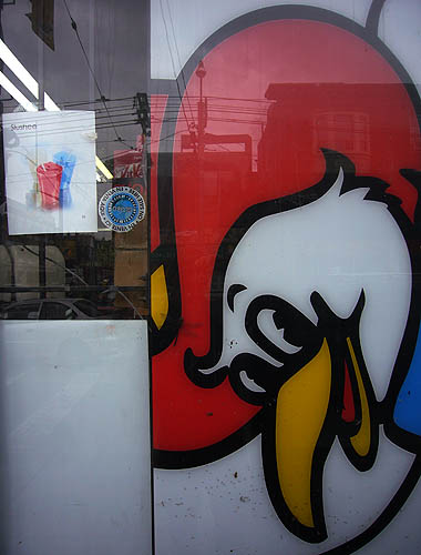 Postings in a shop window show a smiling chicken in a red cowboy hat and a letter-sized ad for Slushee