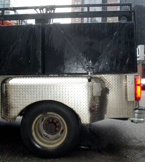 Rear of rain-spattered pickup truck is made of stubbly corrugated steel, with black walls extending upward from the sides of its bed